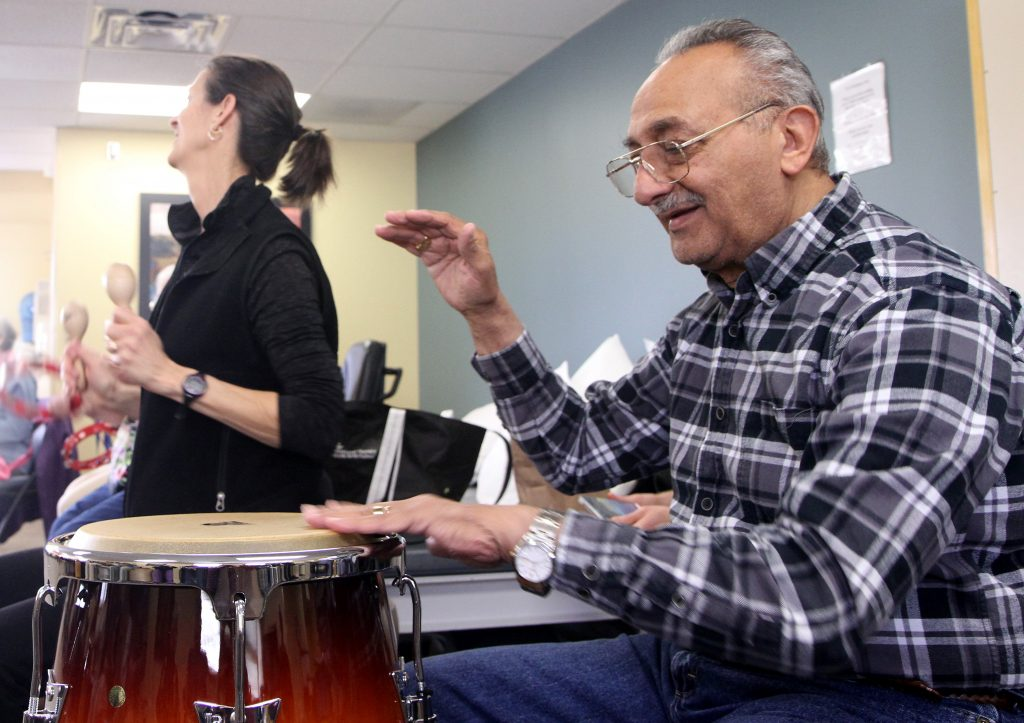 UCHealth music therapy participant Nabil Tadros plays the drums during physical therapiest Ruth Rice's (background) session one Friday morning.
